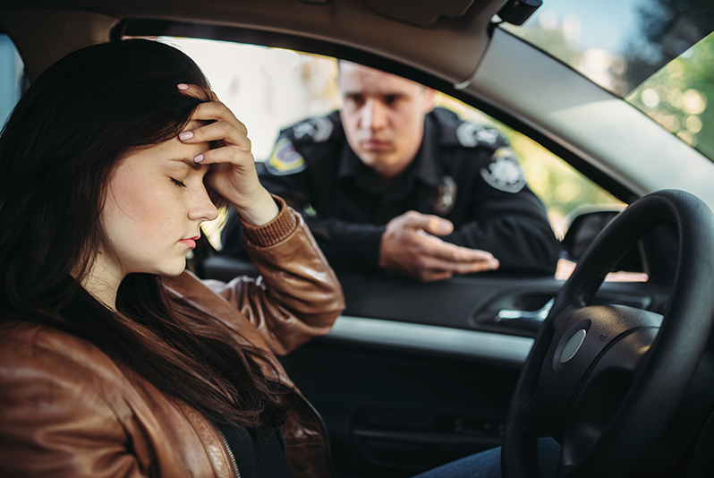 Woman at wheel of car upset with cop in window