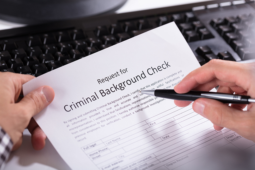 person holding a paper that requests a criminal background check