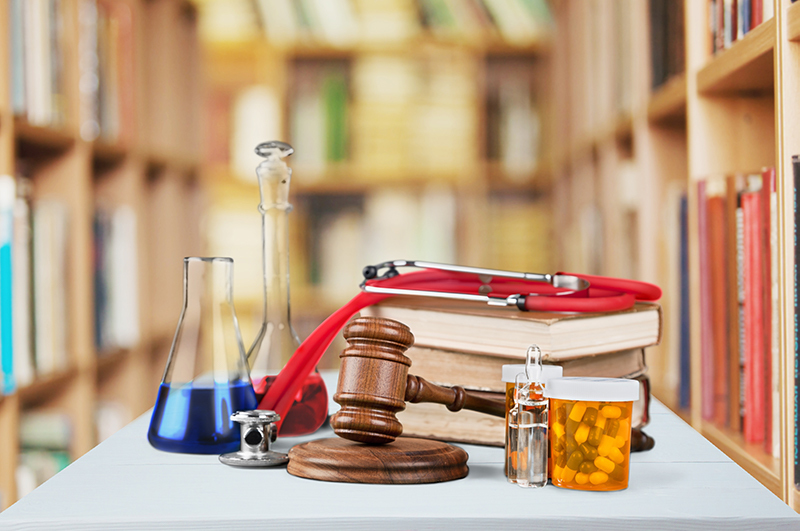 Table with prescription bottle, gavel, and books in front of library shelves