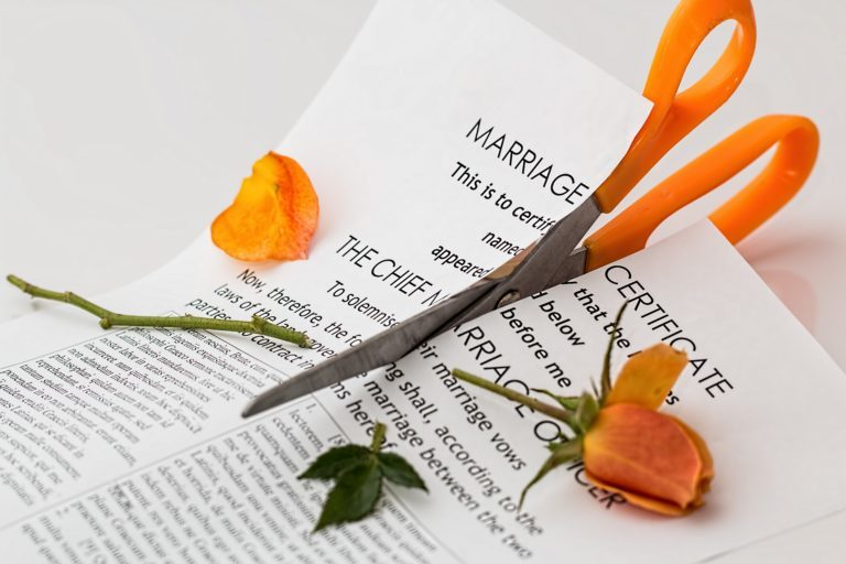 Scissors cutting a marriage certificate paper and flower
