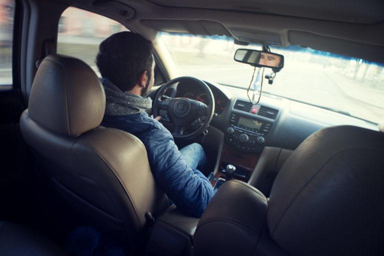 Man inside car, driving.