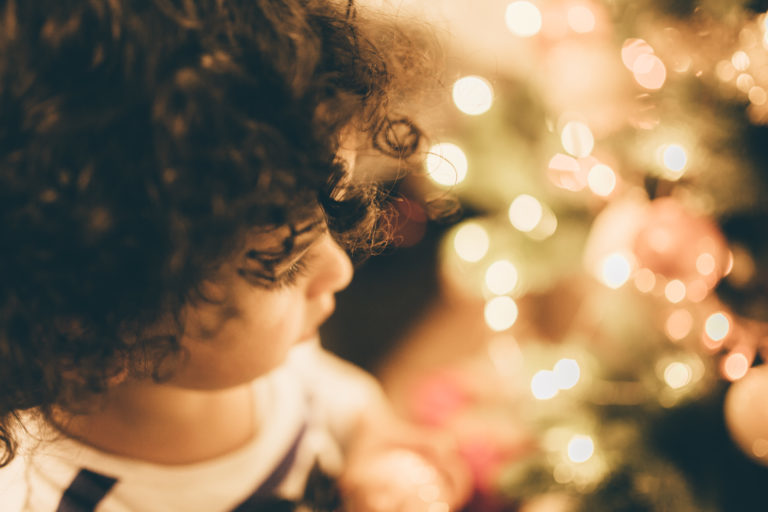 Child standing next to a Christmas tree