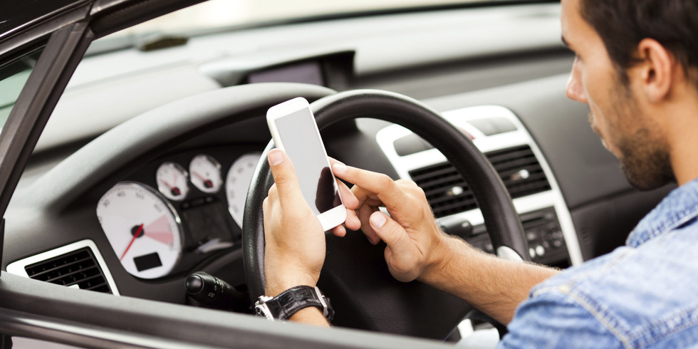 Man driving a car while using his phone