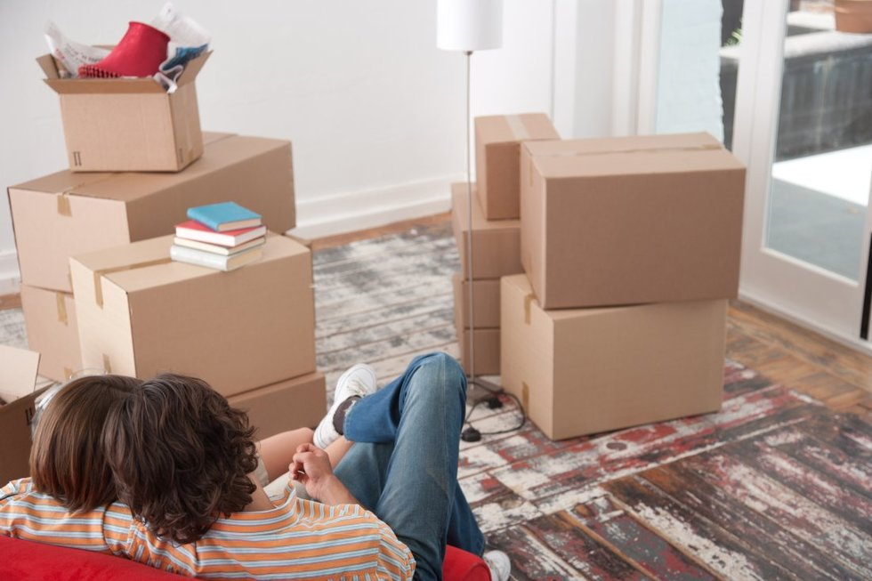 Man and woman in a relationship sitting next to moving boxes