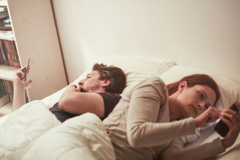 Man and woman laying in bed, both using their phones, turned away from each other,