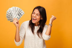 Stock photo portrait of a cheerful young woman holding money banknotes and celebrating isolated over yellow 1038717511