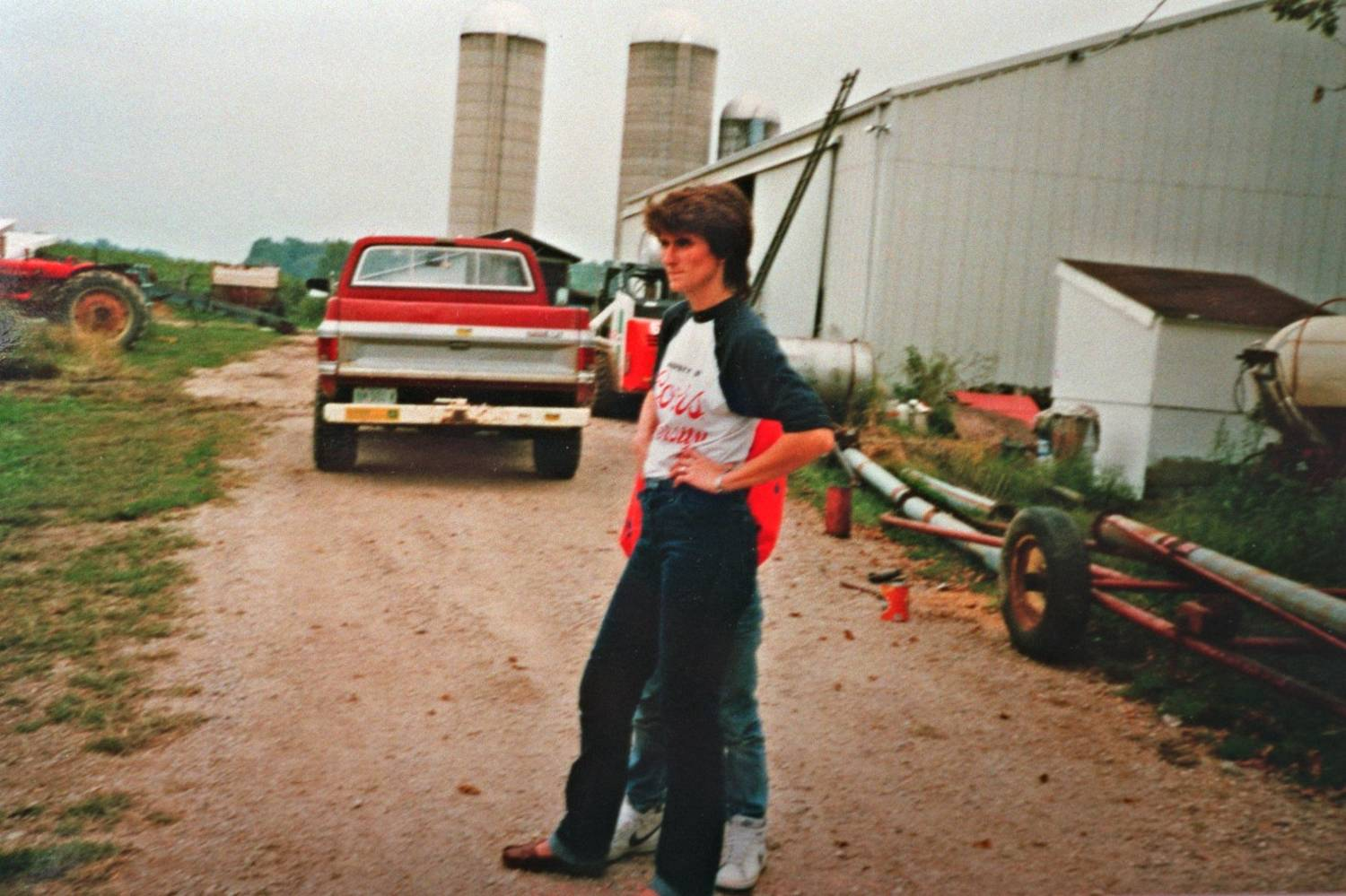 A woman dressed in a long-sleeved t-shirt and jeans stands outside, with farm equipment and grain silos in the background.