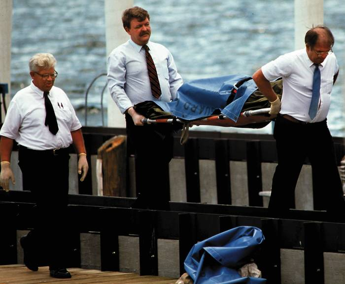 Three men wearing ties walk on a dock. Two are carrying a stretcher with a blue body bag on it.