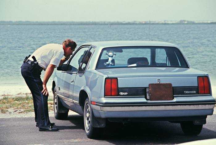 A uniformed policeman inspects a car parked near Tampa Bay.