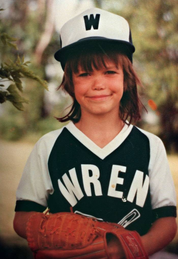 A young girl in a softball uniform and cap smiles into the camera.