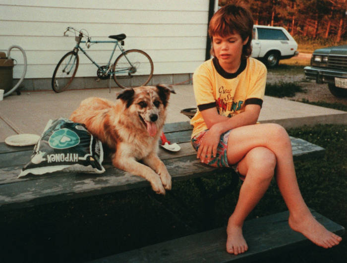 A girl and a dog sitting on a porch step.