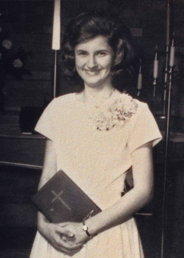 A young woman smiles, holding a Holy Bible.