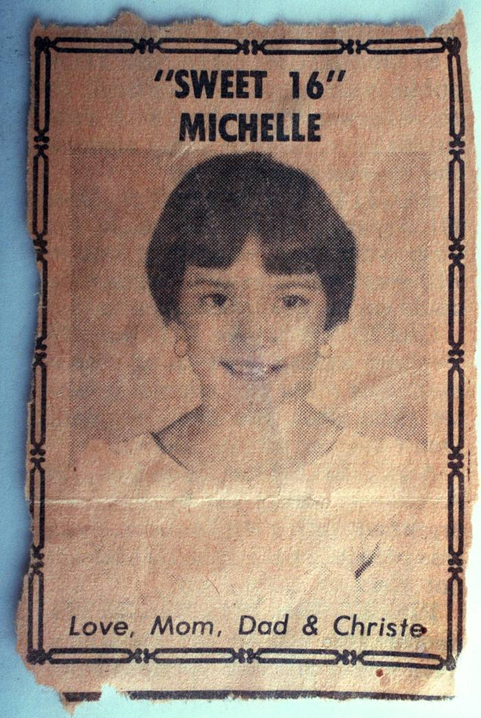 "A yellowed newspaper clipping with a picture of a young woman, and reading ""'SWEET 16 MICHELLE,' Love, Mom, Dad & Christe."""