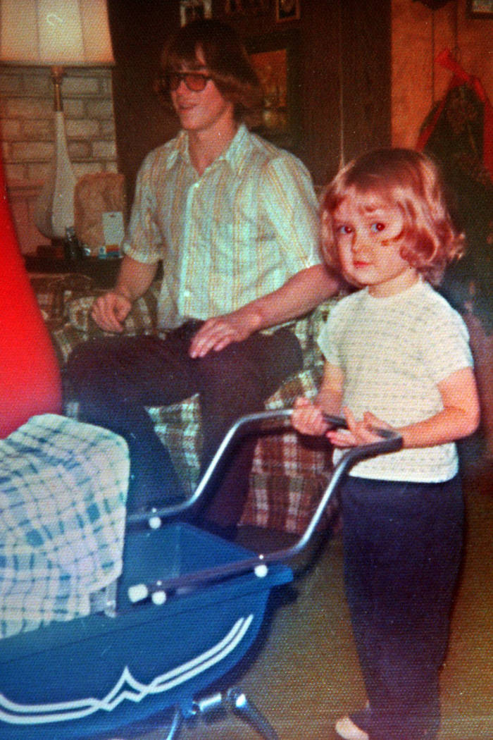 Young girl pushes blue baby carriage, in the background is an adult man sitting on a couch.