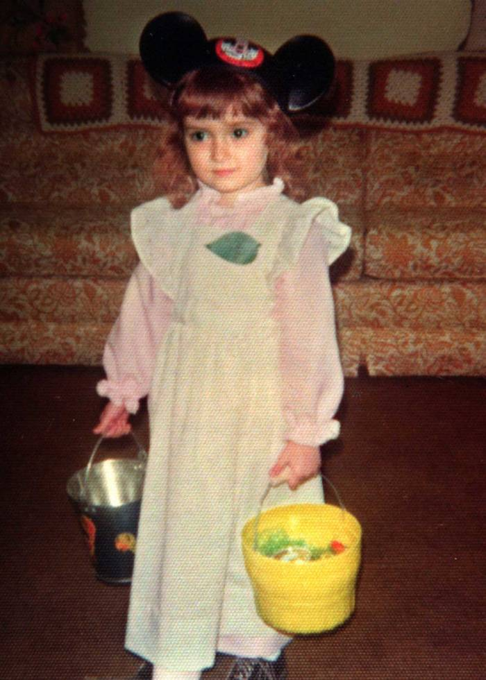 A young girl wearing mouse ears stands carrying buckets of candy.