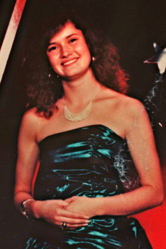 A happy young woman in a shiny blue prom dress smiles broadly.