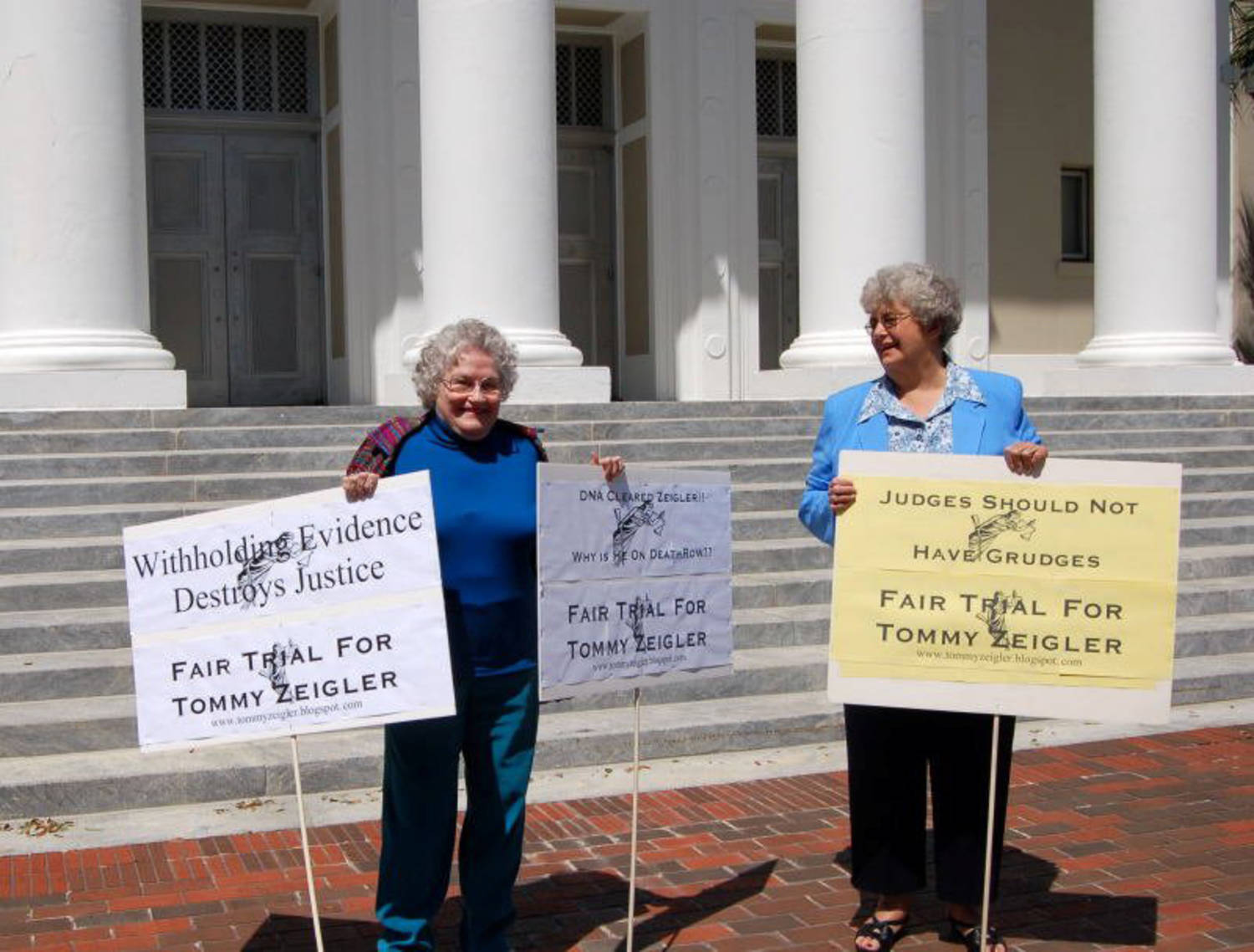 Two older women standing in front of courthouse steps and columns, holding picket signs supporting Tommy Zeigler.
