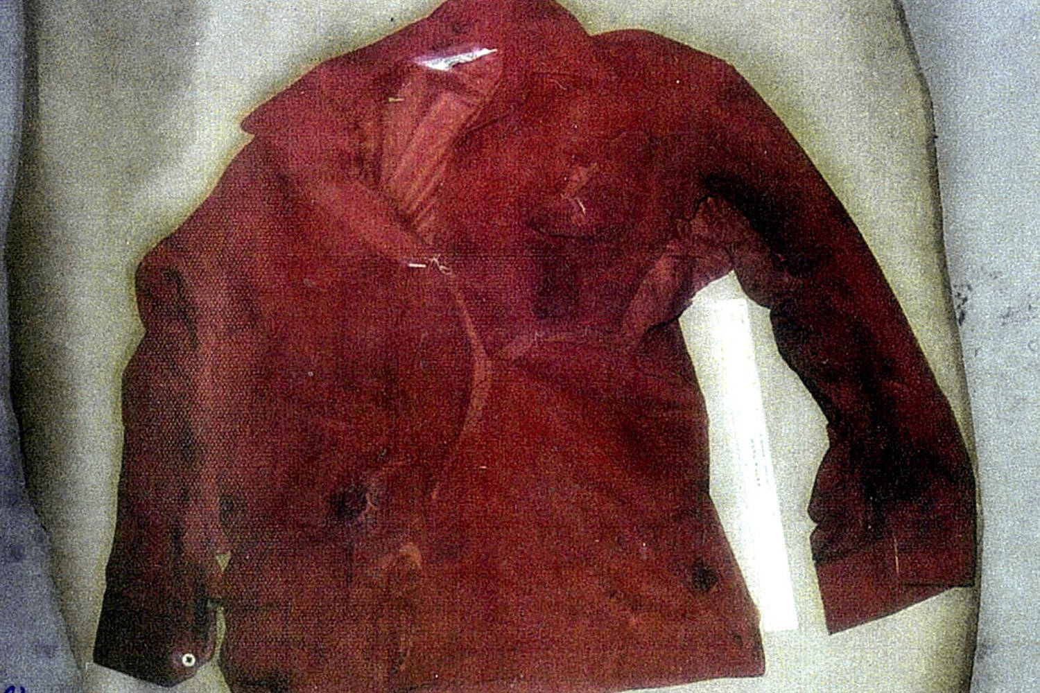 Police evidence photo of a long-sleeved red shirt. It has been cut open, and there is a bullet hole near the stomach.