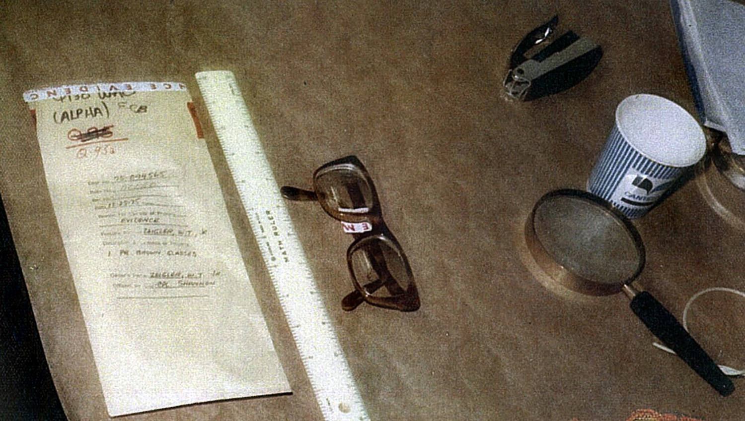 Evidence photo of a pair of glasses, with a ruler alongside for comparison.