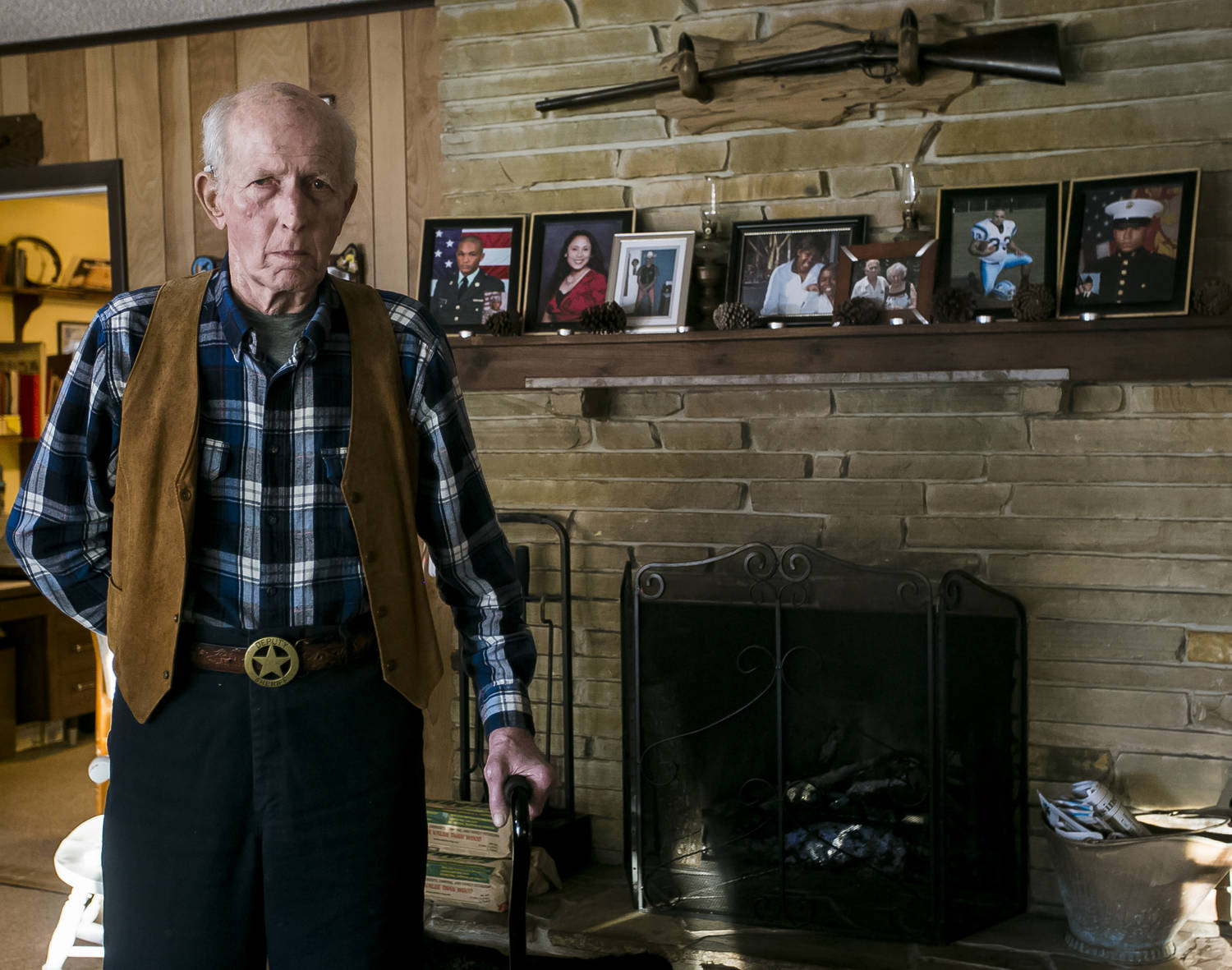 An older man, steadying himself with a cane, stands in front of a hearth, with framed photos of people on the mantle. Above the fireplace is hung a rifle. He is wearing a flannel shirt, leather vest, and a brass belt buckle with a sheriff's star.