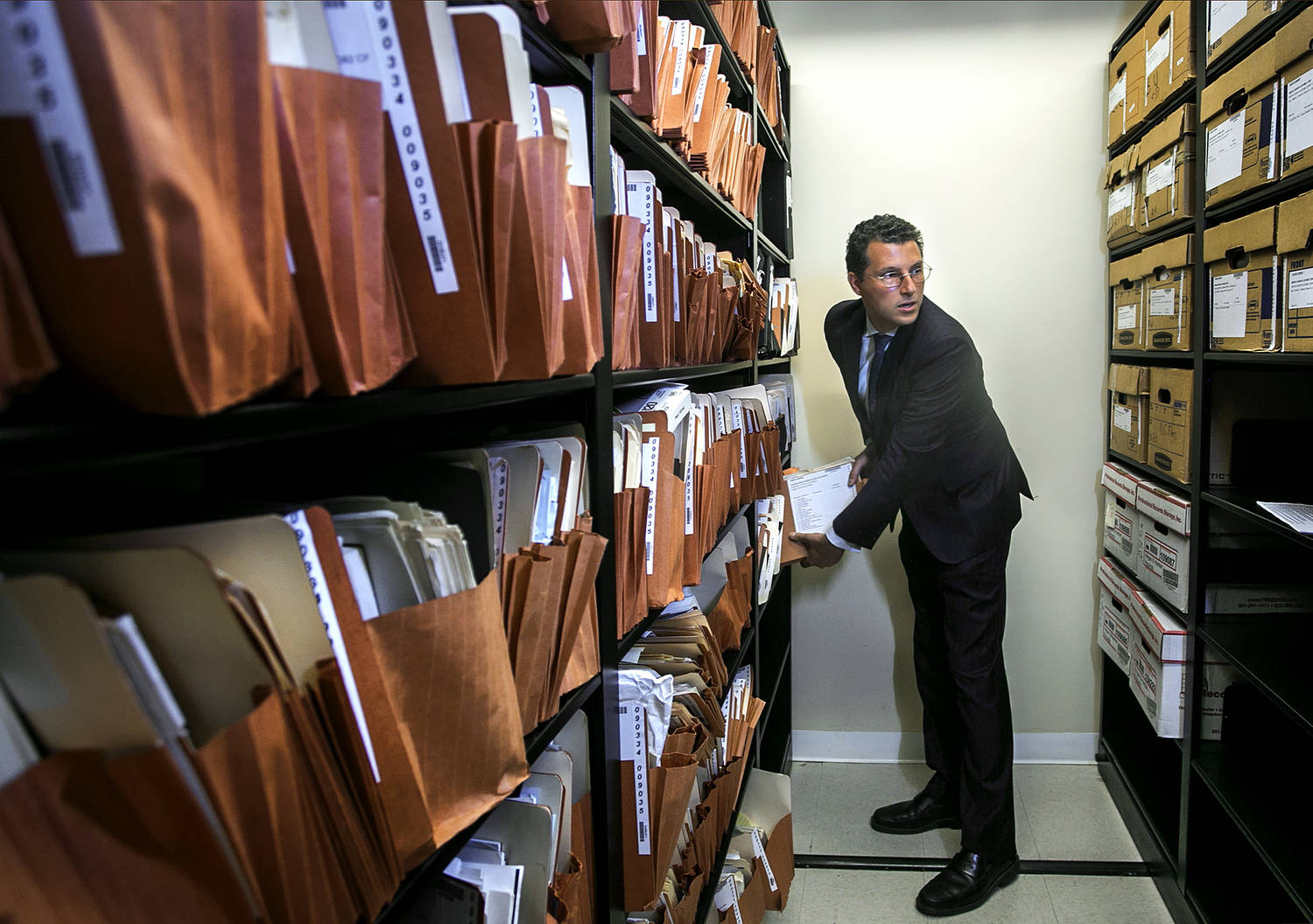 Between shelves of file folders and document storage boxes is a man in a dark suit, pulling a group of files from the shelf.