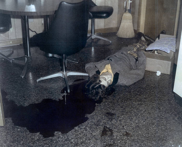 Police evidence photograph of a dead woman with blood on the floor around her head