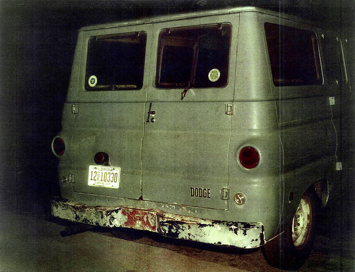 A flash-illumnated photograph of the back of a well-worn green van, showing the license plate.