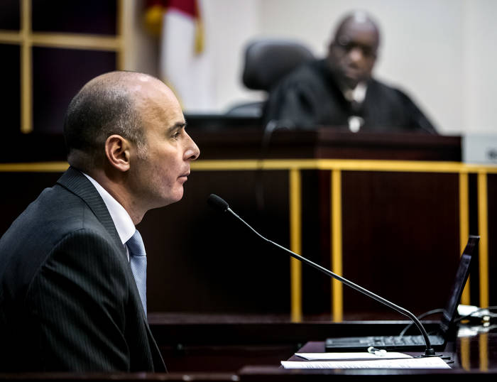 A man at the witness stand, seen from his right side, wearing a suit, looks straight ahead. In the background, out of focus, is the judge.
