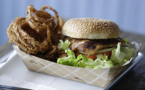 Blackened grouper sandwich, onion rings. [JAMES BORCHUCK  | Times]