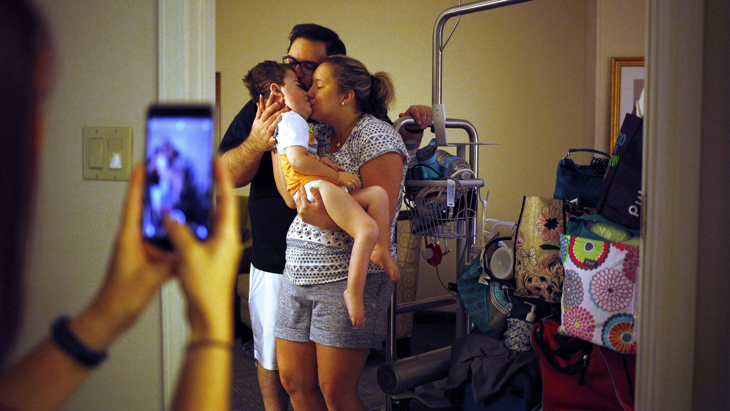 In the foreground, someone using a cellphone to take a picture of the couple standing holding their baby in a hospital room.