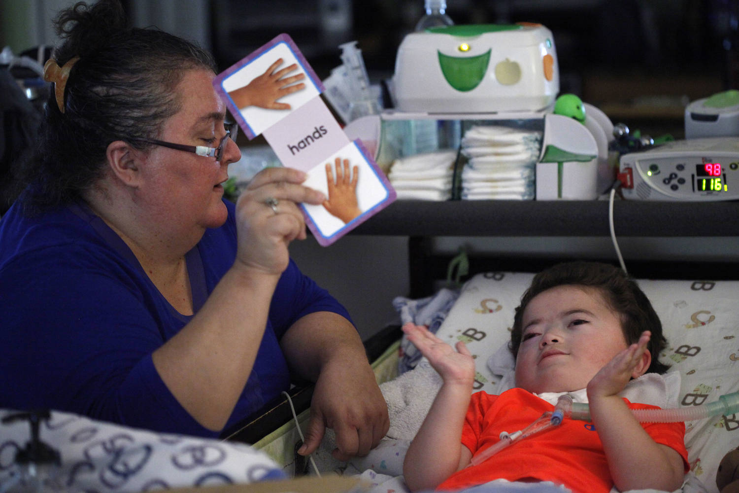"The child lays in his bed, showing his hands. Beside the bed is a woman holding a flash card with pictures of hands and the word ""hands."""