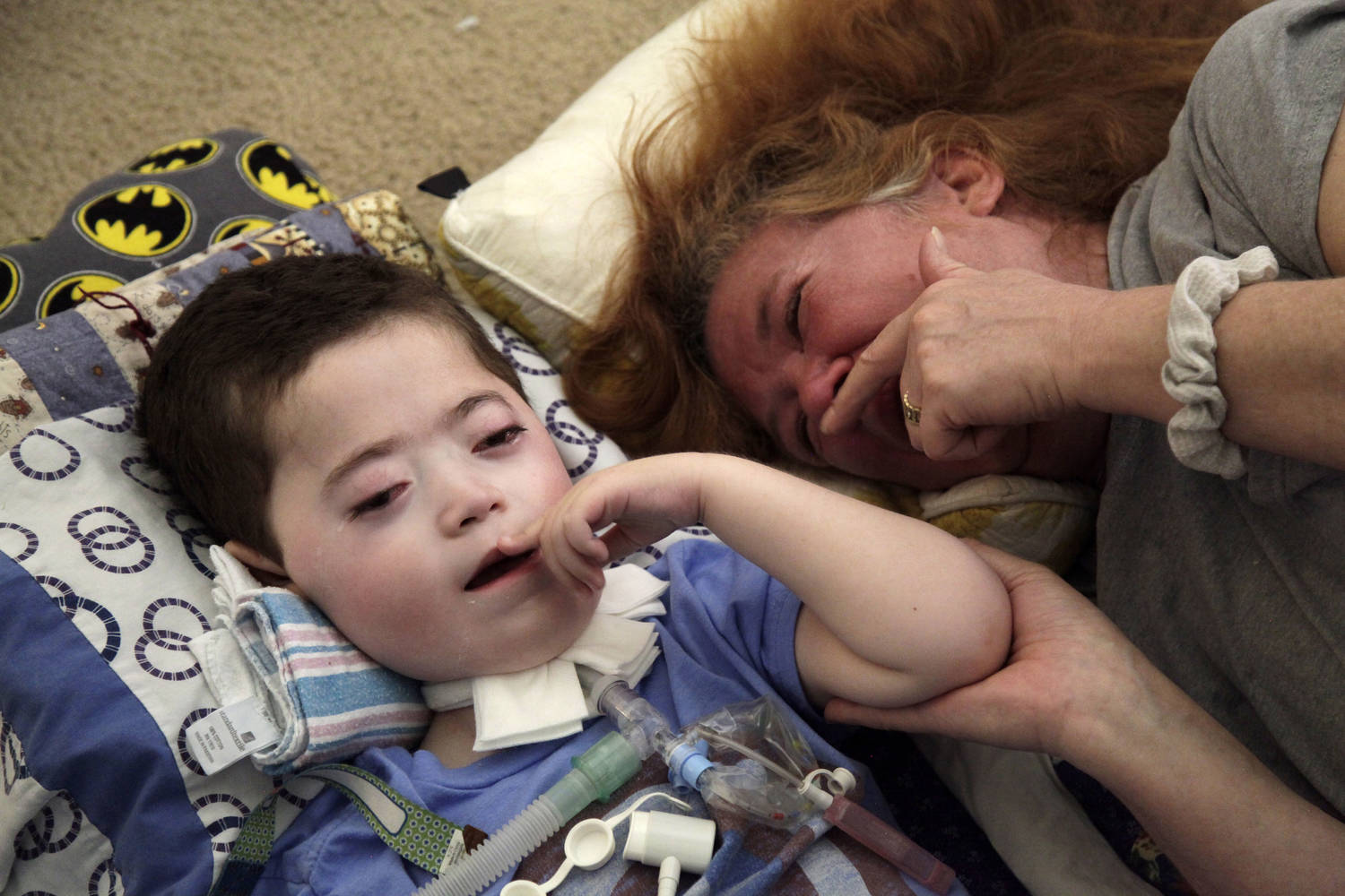 A woman showing her emotion lies on the floor next to the child, staring at him and holding his arm.