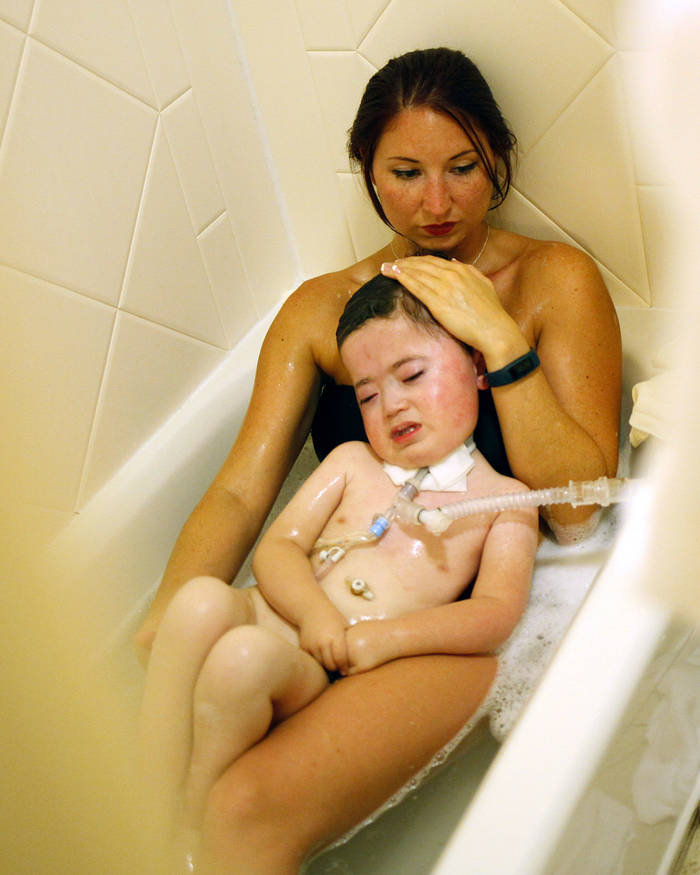 A woman lies in a bathtub, giving the boy in her lap a bath. She is wearing a bathing suit.