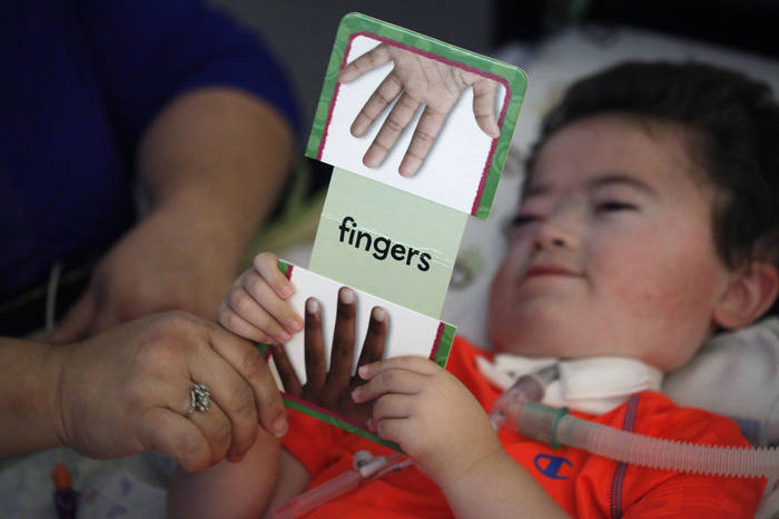 "The child, in bed, holds the flash card with ""fingers"" written on it."