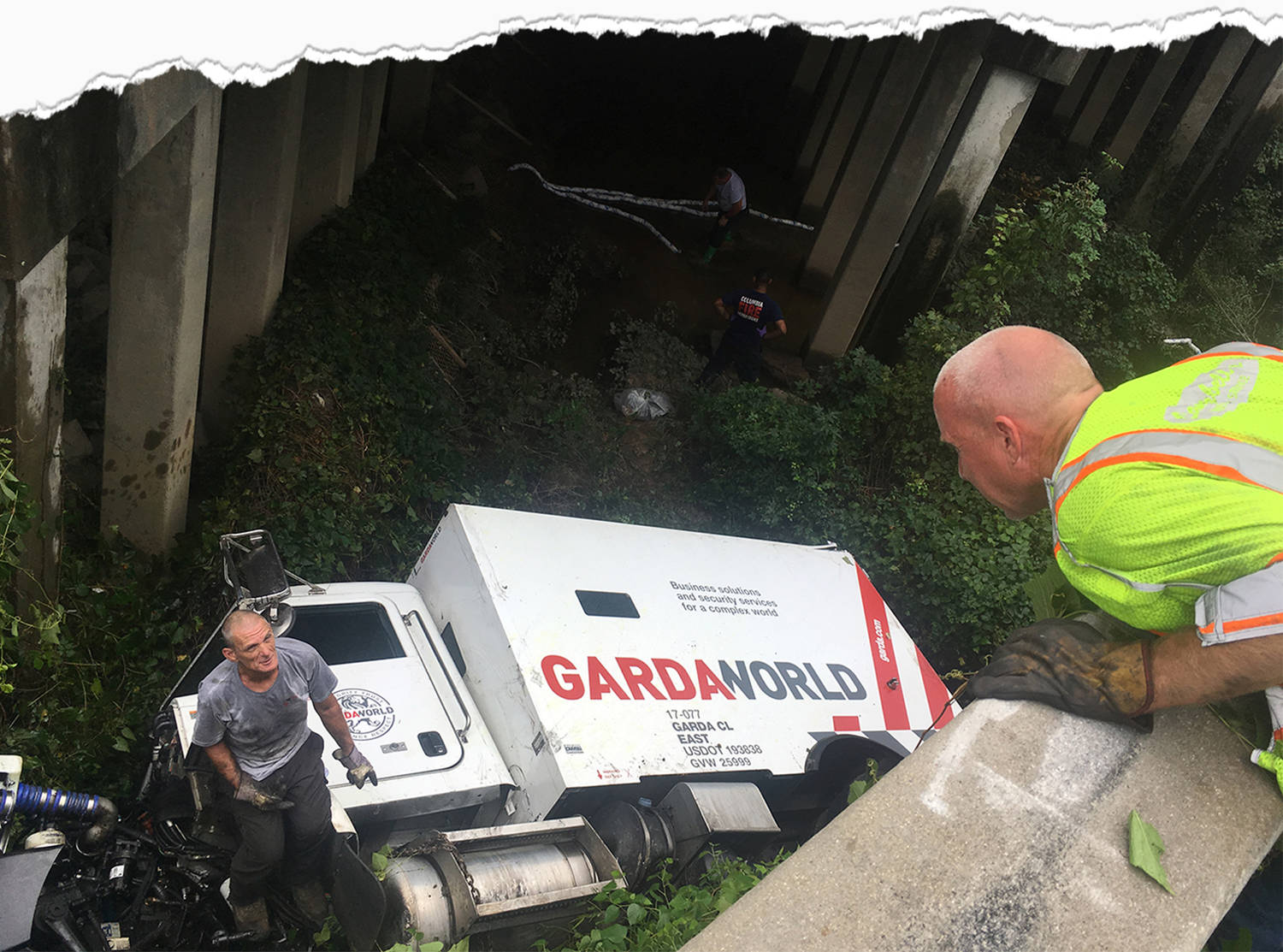 As one worker wearing work gloves and a yellow vest leans over a low concrete barrier, another worker well beneath him stands on an overturned Garda armored truck in the weeds, having apparently driven off the roadway.