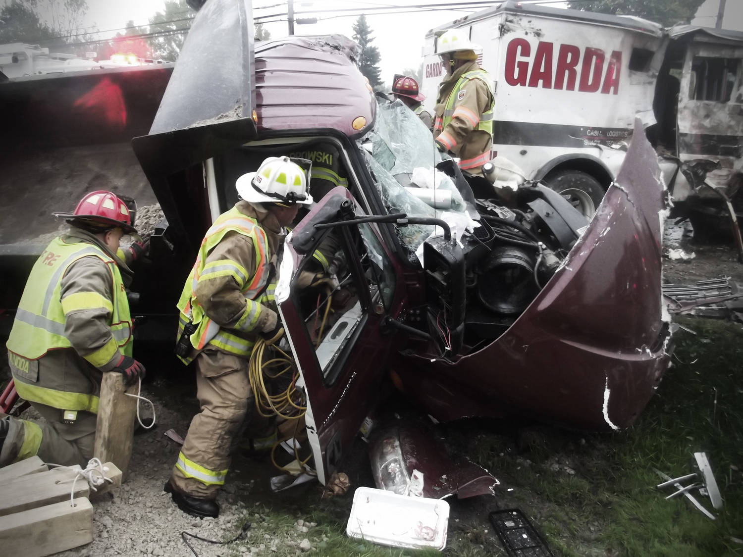 Firefighters working at the scene of a terrible wreck to extract a victim from the cab of a mangled truck.