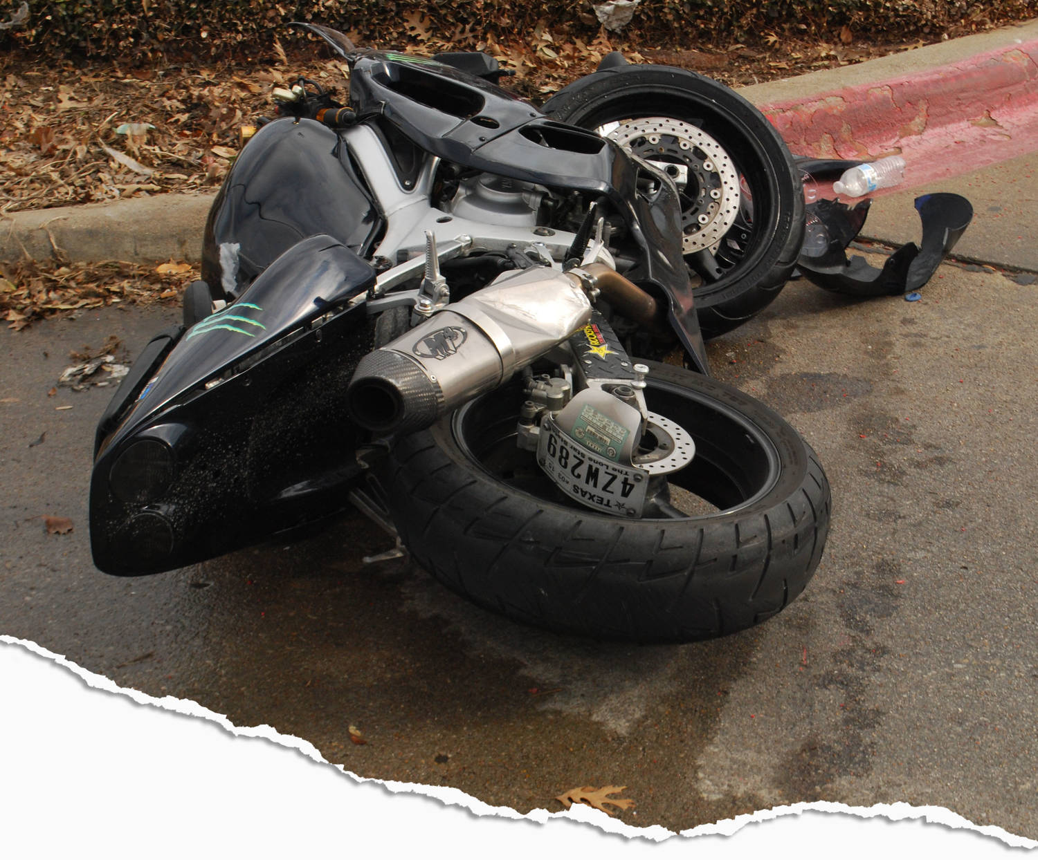 A smashed motorcycle in the road.