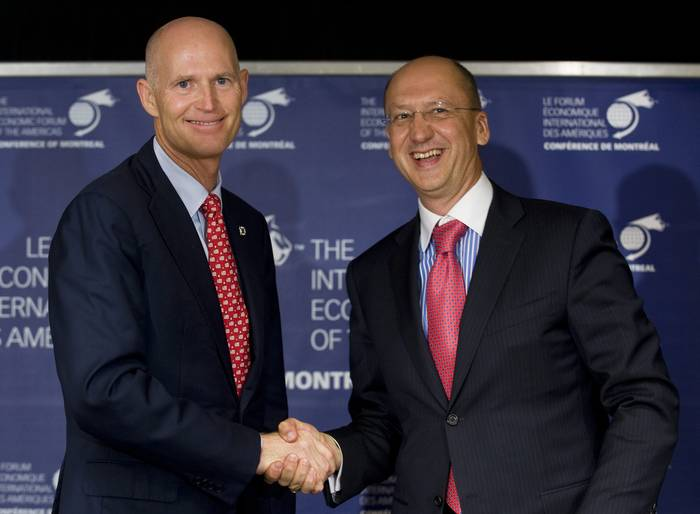 Two standing mostly-bald men wearing blue suits and red ties perform a grip-and-grin for the cameras.
