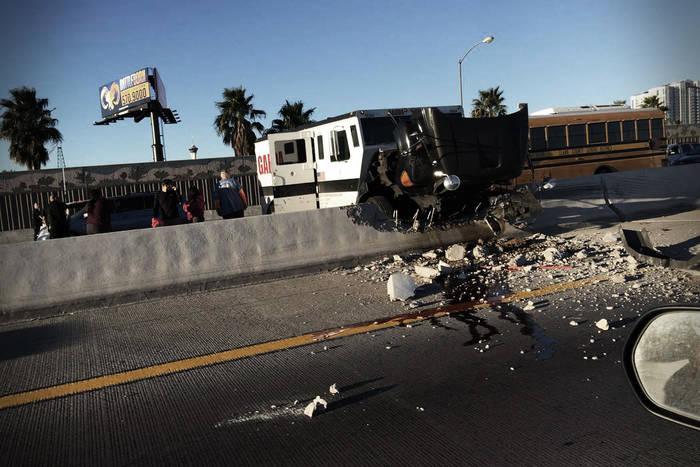 A Garda armored truck crashed into a highway divider, scattering broken concrete on the roadway.