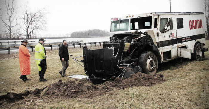 A Garda armored truck with lots of front-end damage sits in a muddy field where it has skidded to a stop.