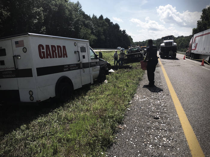 A Garda armored truck in a highway median, tow truck and stopped semi-truck nearby.