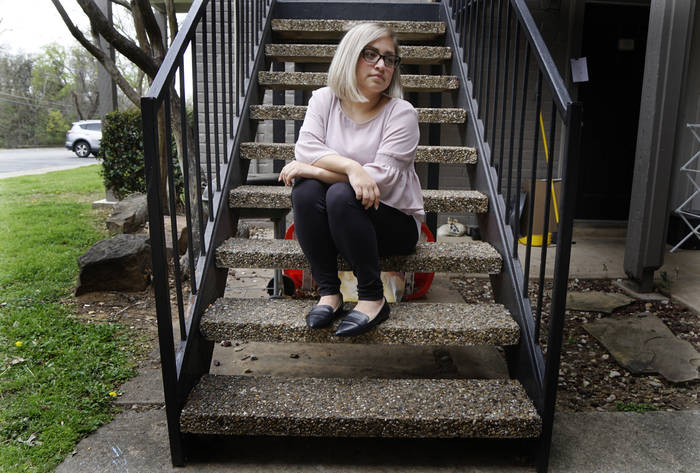 A woman sits on the stairs.