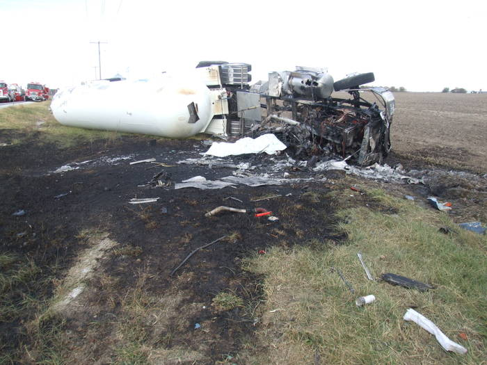 An overturned tanker truck, the cab mostly consumed by fire that spread to the grass it lies on.