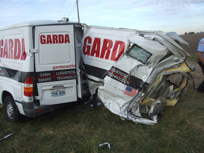 A crashed Garda armored truck, the right side peeled nearly completely off.
