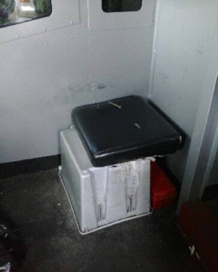 An overturned plastic bin with a seat cushion on top inside the riveted steel walls of an armored truck.