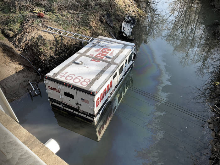 Seen from an overpass above, a Garda armored truck sits partially submerged in a slow-moving creek, a sheen of oil on the water.