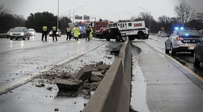 A Garda armored truck straddles a concrete highway barrier, in the foreground the barrier is broken, large chunks of it laying in the highway.