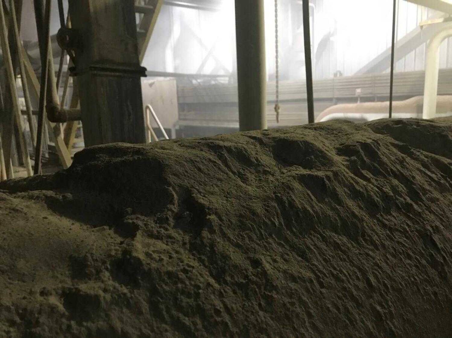 Mounds of dust pile high along a ventilation pipe that runs above workers' heads in the furnace department.