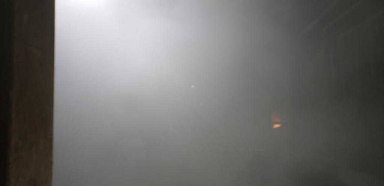 A photo of the furnace where nothing is visible except a small speck of orange light amidst the grey-washed haze of airborne lead dust.