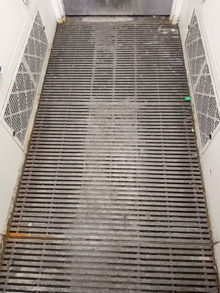 A photo of a slotted floor in the airshower where dust is blown off of employees after their shift.